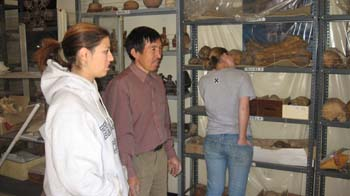 Danielle and Lorenzo are looking to the right at something. There is a person behind them with their back to the camera. There are blue shelves with skulls and artifacts. The shelves have clear plastic covers. Danielle is wearing a white sweatshirt with blue lettering. Her brown hair is in a ponytail. Lorenzo is wearing a purple long sleeved shirt and khakis. He has black hair and a beard. The person in the back is wearing a gray t shirt and jeans.