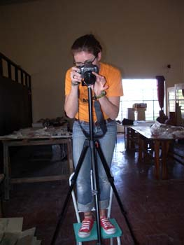 Cat is standing on a blue chair behind a camera. She is looking into the lens. There are two long tables in the room behind her. She is wearing an orange shirt, jeans, glasses, and red shoes. Her brown hair is in a ponytail.