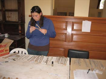 Ellen looking at fibulas. She is holding two and there are more laid out on the table. There is a large wooden dresser behind her. There is a dark wooden desk with cabinets on the top in the back left. Ellen is wearing a blue long sleeved shirt, with a brown stripe along the bottom, jeans, and sunglasses on her head. She has shoulder length brown hair.