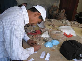 Jimmy is making labels on white paper. The table has various objects on it- blue face masks, vertebra, a black bag, plastic, and a white bag. Jimmy is wearing a white collared shirt with with black lines making squares. He is wearing a white baseball cap. He has short black hair.