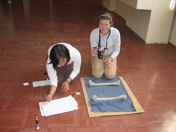Katie and Cat are sitting on a red tiled floor looking at femurs. The bones are on a piece of cardboard and a blue piece of paddings. Katie is hunched over and writing on paper. Cat is holding a camera. Katie is wearing a white shirt and brown pants. Her black hair is chin length. Cat is wearing a blue-ish long sleeved shirt, khaki pants, and a white headband. She has brown hair pulled back.