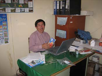 Lorenzo sitting in front of a gray laptop o a green table. He is smiling into the camera and holding something with a blue cover. There is a pile of papers by the computer. He is wearing a red long sleeved shirt. He has short black hair and a mustache.