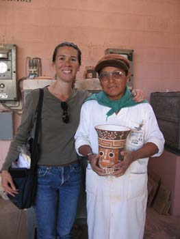 Tiffiny and Juan are smiling into the camera. Juan is holding a repllica of a Wari ceramic- it is a cylinder that gets wider at the top. It has an orange face. There are orange square like squiggles on a white background above the face. Above that is a thick brown rim at the top. It's white inside. Tiffiny is wearing a green long sleeved shirt, jeans, and has a black bag over her shoulder. There are papers sticking out. She has sunglasses hanging from the collar of her shirt. Her brown hair was in a ponytail. Juan is wearing a lab coat, a brown hat, glasses, and something green tied around his throat.