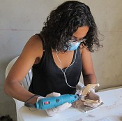 Kristina is wearing a black tanktop, glasses, a blue mask, and white gloves. She has curly black hair. She is holding a drill in one hand and a jaw bone in the other. She is looking down at them.She is sitting in a white chair and a white table.