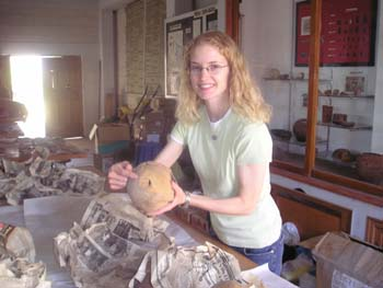 KC is smiling into the camera, holding a skull, and pointing to an abrasion on the back of it. There is newspaper on the table in front of her that it was wrapped in. She is wearing a mint tshirt, glasses, and jeans. She has shoulder length blonde curly hair.