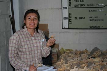 Mirza is sitting in front of a table of bones and is holding one in each hand. She is smiling into the camera. She wearing a brown shirt with red outlines to a square pattern and jeans. Her black hair is in a ponytail.