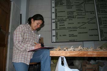 Mirza is sitting in front of a table of bones. There is a white plastic bag hanging off the side. She is looking down at the clipboard in her lap. She wearing a brown shirt with red outlines to a square pattern and jeans. Her black hair is in a ponytail.