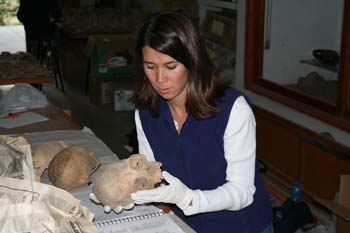 Tiffiny is holding a skull. There is a book, another skull, and newspaper. She is wearing a white long sleeved shirt, blue vest, and white latex gloves. She has shoulder length brown hair.