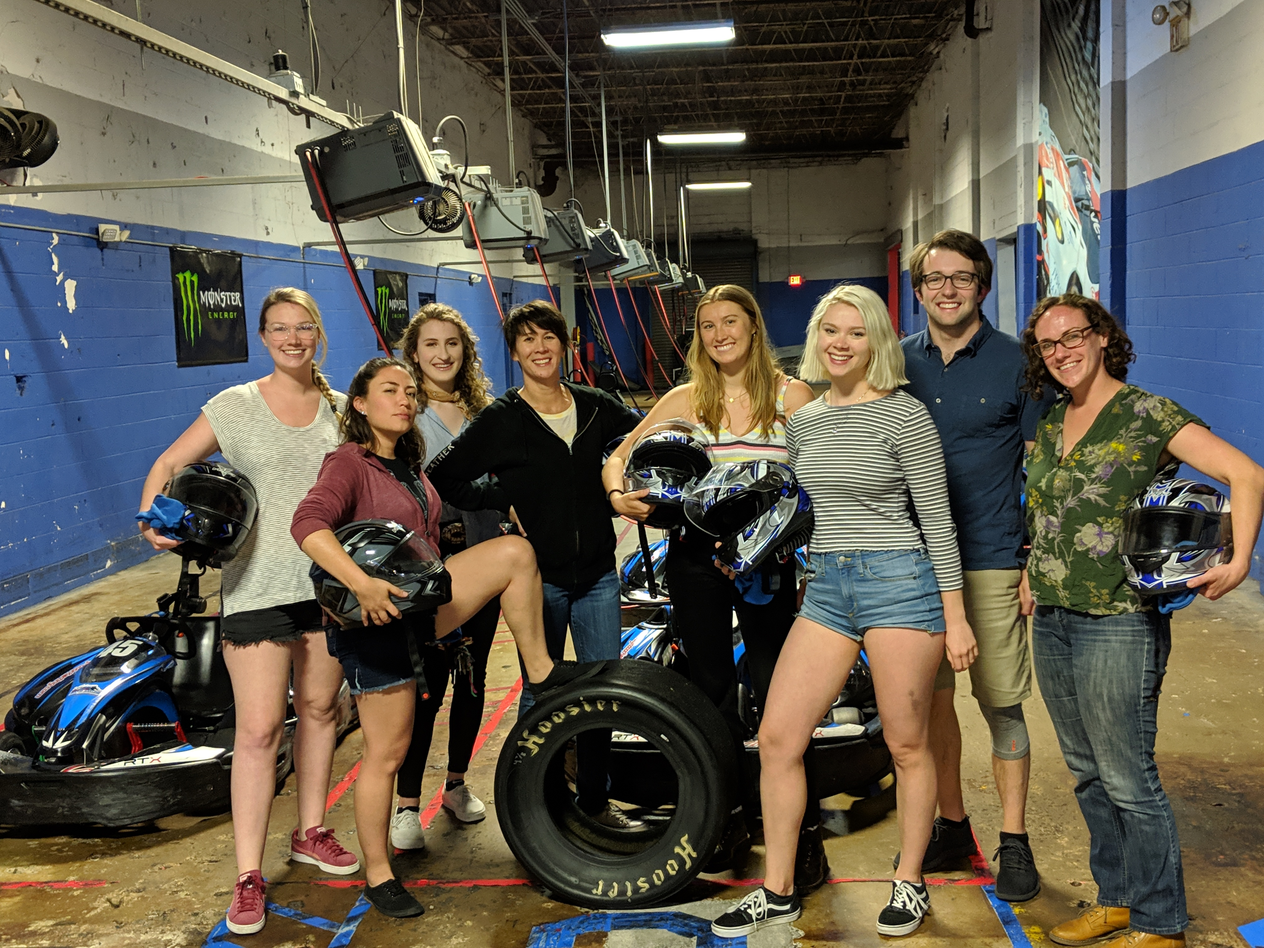 A student, Keitlyn, another student, Tiffiny, Maya, Anna, Tom, and another student who help in the lab at an indoor GoKarting place. They are all smiling into the camera. The ground is concrete and the walls are made of cement bricks. The wall is painted blue most of the way up and then white the last of the way. There are two blue GoKarts behind the group. The first student, Keitly, Maya, Anna, and the student on the far right are holding blue and black helemets. The first student is wearing a gray tshirt, black shorts, red shoes, and glasses. Her blonde hair is in a braid. Keitlyn is wearing a red jacket, jeans shorts, and black shoes. Her foot is up on a black tire. She has shoulder length brown hair. The next person is wearing a blue shirt and has curly blonde hair. Tiffiny is wearing a black jacket, white undershirt, and jeans. She has short brown hair. Maya is wearing a white tanktop and black pants. She has long blonde hair. Anna is wearing a longsleeved gray shirt, jean shorts, and black and white shoes. She has bleach blonde cin length hair. Tom is wearing a blue polo, khaki pants, black shoes, and glass. He has short brown hair. The last student is wearing a green shirt with gray and light green designs on it, jeans, brown shoes, and glasses.
