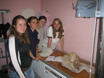 Rachel, Ella, Ellen, and Emily around the table with the mummy on it in the xray room. They are all smiling into the camera. There is x ray equipment above the mummy. Rachel is wearing a black jacket with a white stripe down the sides and jeans. She has long curly brown hair. Ella is wearing a navy shirt and jeans. She has brown hair pulled back. Ellen is wearing a gray shirt. She has dark hair pulled back. Emily has a white t shirt with a black collar and black around the bottom of the sleeves.