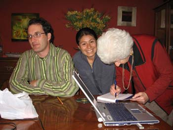 Steve, Mirza, and Maria Benavides sitting at a table. Maria is signing a copy of a book she wrote. Steve is looking to the left and Mirza is smiling into the camera. There is a silver and blue laptop on the table as well as a white plastic bag. Steve is wearing a dark green, light green, and brown vertical striped shirt. He is wearing glasses and has short brown hair. Mirza is wearing a blue zipped up jacket. Her black hair is in a ponytail. Maria (right) is wearing a red shirt, red and black jacket, as well as a gold necklace. She has white hair.