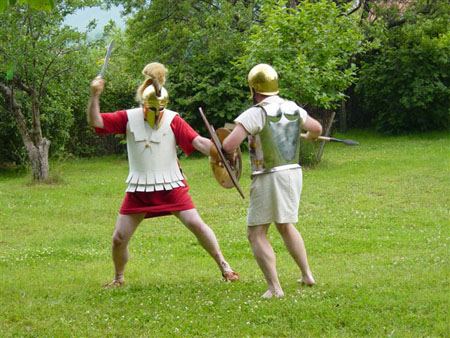 Two people with weapons and armor are standing in a green field. They are both holding a shield and spear. The one on the left has a red garment down to their thighs. Their brestplate looks like it's made of paper. They have a golden gladiator style helmet on. The one on the right is wearing a white garment and a golden helmet.