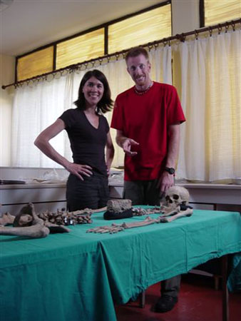 Tiffiny and Ken standing over a skeleton laid out on a table with a teal table cloth. Tiffiny is smiling into the camera with her hands on her hips. She is wearing a purple shirt and black pants. Ken is pointing at the skeleton and smiling into the camera. He is wearing a red shirt and gray pants.