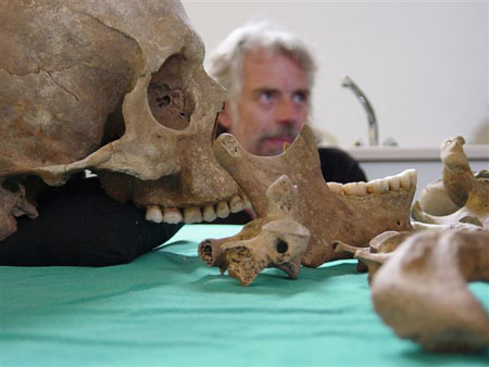 A side view of the skull, jaw, and some of the upper bones in the body on a teal table cloth. Peter is out of focus in the back ground. He is wearing a black shirt and has gray hair.