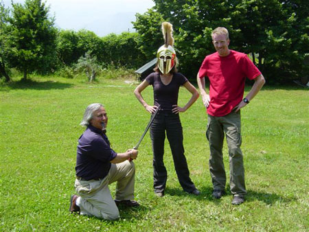 Theo is kneeling on the ground in a green field with trees. He is pointing a fake sword at Tiffiny. Tiffiny- with a golden gladiator style helmet on her head- and Ken are both standing with their hands on their hips. All of them are looking into the camera. Theo is wearing a purple shirt and khakis. He has long gray hair. Tiffiny is wearing a purple shirt and black pants. Ken is wearing a red shirt and gray pants. His blonde hair is flat.