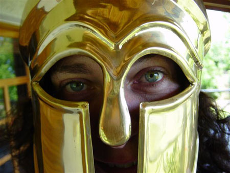 Kate is wearing a golden gladiator-style helmet. You can see her blue eyes and part of her mouth. Her black hair is sticking out the bottom.