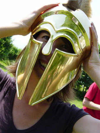A close up of Tiffiny in the gladiator-style helmet. She is wearing a brown shirt.