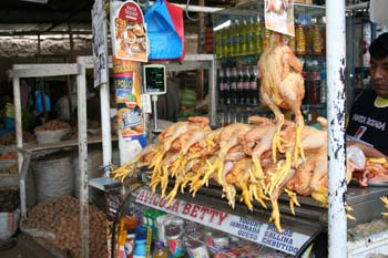 A pile of skinned chickens on a market stand. One is hanging from the stand. There are drinks under the table.