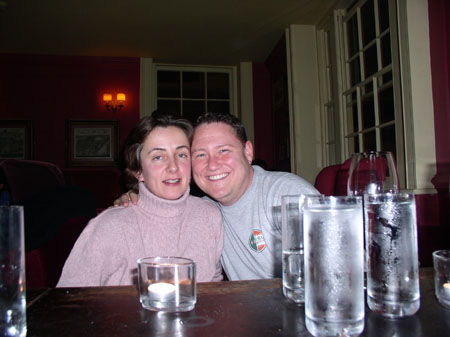 Ruth and James M are sitting at a table. Their faces are squeezed together and James' arm is around Ruth's shoulder. Ruth (on the left) is wearing a pink turtleneck. James is wearing a gray tshirt. There are cold glasses of water on the table.