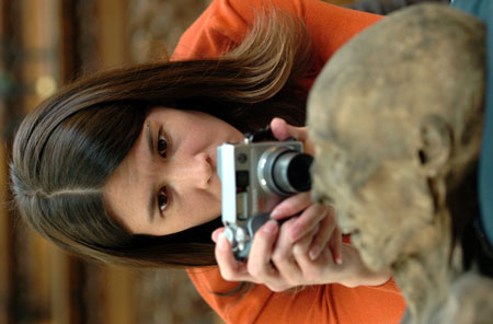 Tiffiny in an orange shirt focusing intently on photographing the head of a mummy.