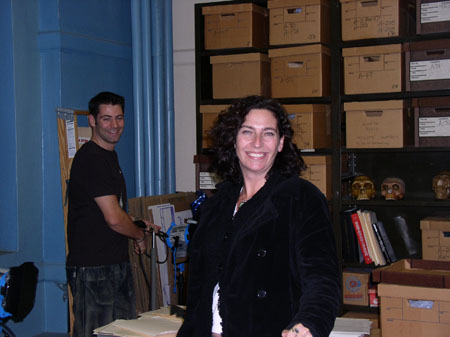 Kate and another person are in the Vanderbilt Osteology Lab. There are boxes, skull casts, and books on blakc shelves. Kate is wearing all black. The other person is wearing a blakc shirt and jeans. They have short black hair.