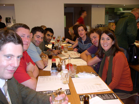 TIffiny, AJ, James M, four other people looking into the camera, and three people not looking into the camera at the end of the table. They are at a restaurant. There are menus and glasses on the table. Tiffiny is wearing an orange long sleeve shirt and a green scarf.