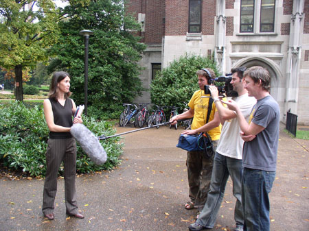 Tiffiny is standing on Vanderbilt University's campus. She is wearing a black vest and gray and black stripped pants. She is holding a book and looking into the camera. The person holding the camera is in the middle of a line of three people. They are wearing a white shirt and jeans. AJ is to the left of the middle. He is wearing a yellow shirt, brown pants, and headphones. He is holding a boom mic to Tiffiny. The person on the right is wearing a gray shirt with something yellow on the front and jeans. They are smiling and pointing at Tiffiny. The building behind them has stone bricks for the first floor and red bricks for what you can see of the second. There are bicycles lined up in front of it. There are trees and bushes.