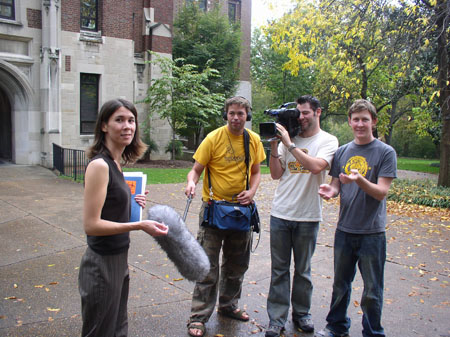 Tiffiny is standing on Vanderbilt University's campus. She is looking into the camera taking the photo. She is wearing a black vest and gray and black stripped pants. She is holding a book and looking into the camera. There is a line of three people. AJ is to the left of the middle. He is wearing a yellow shirt, brown pants, and headphones. He is holding a boom mic to Tiffiny. In the middle, a person holding a camera on Tiffiny is T wearing a white shirt and jeans. The person on the right is wearing a gray shirt with something yellow on the front and jeans. They are gesturing at Tiffiny and looking into the camera taking the photo. The building to the left of them has stone bricks for the first floor and red bricks for what you can see of the second. There are trees and bushes.