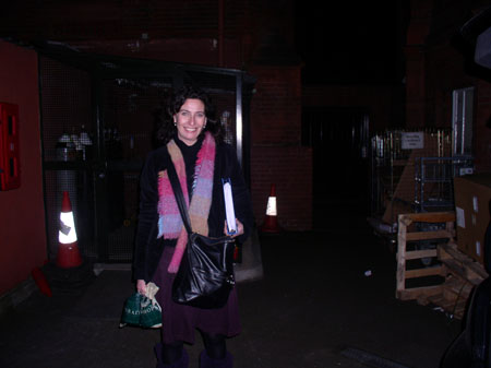Kate with a black jacket, prurple skirt, and a colorful scarf in a darkly lit room. She is holding a book in one hand and a green bag in the other. She had a black bag across her body. She is smiling into the camera.