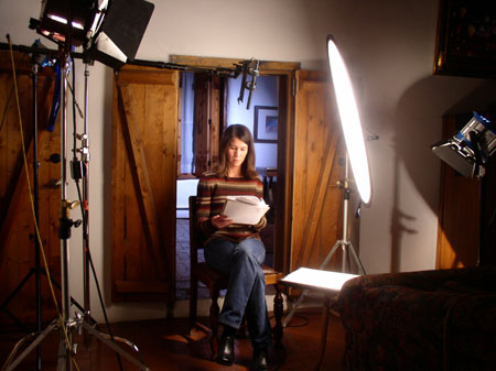 Tiffiny sitting in a wooden chair. There are three bright lights shining on her and a mic above her. She is looking at the book she is holding. She is wearing a multicolored striped sweater. Behind her are two open wooden doors with another room behind it.