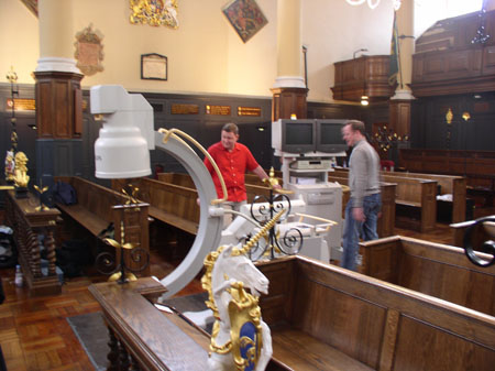 Two people are setting up x-ray equipment in what looks to be a church. There are wooden pews and candle holders all over the room. In the foreground there is a sculpture of a white and gold unicorn. The person on the left is wearing a red shirt and jeans. They have brown hair. The person on the right is wearing a gray shirt and jeans. They have brown hair.
