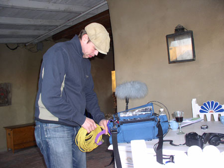 AJ is wearing a beige hat, a blue jacket, and jeans. He is holding a wrapped up yellow cord coming from a boom mic sitting on the table.