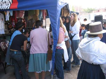 A crowd of people is around a tent at the Museo De Memoria.