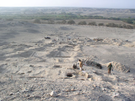 A rocky and sandy field. There are piles of both lying around of different sizes. There is a circular hole towards the front and there are two people by the hole. There is a person standing near them to the right. There are three square shaped holes in the ground. Around the furthest one is maybe 10 people but they are far away. In the background there are trees and a hill.