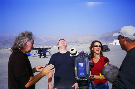 Peter, James M, Tiffiny, and Les (left to right) are standing around a camera. James S and Tiffiny are in front of it. Peter and Les are to the sides. Peter is holding something and looking at it. He is wearing a black shirt and has long gray hair. James S is looking at the sky and laughing. He is wearing a navy t-shirt. Tiffiny is looking at Les and laughing. She is wearing a red shirt and sunglasses. Les is wearing a navy tshirt and a white baseball cap. You can't see his face.