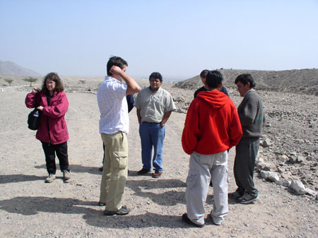 Kathy is person wearing a pink jacket. They are holding a large black bag and has brown hair. Her name might be Kathy. There are six people standing in a circle on the left. They are all standing on a rocky path, but there is larger rocks on either side of it.