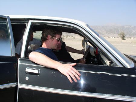 Four people are sitting in a black car with colorful bobbles hanging from the rear view window. James M is sitting in the front passenger seat- the closest to the camera. He is weraing a navy t-shirt and sunglasses. His arm is sticking out the sinder and he is looking at the dashboard. He has short brown hair. Mike is sitting in the drivers seat. He is wearing a black t-shirt and has gray hair on his head as well as his beard. He is looking under the steering wheel. There are two people in the back seat but you can't really see their faces. On the passenger side, the person in wearing glasses. The window is up an dmakes them hard to see. The other person is wearing a white t-shirt and khaki baseball hat.