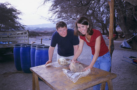 James M and Tiffiny are crouched over a table. There is a skull and a rock on the table. James is wearing a navy t-shirt and khankii pants. His hair is short and brown. Tiffiny is wearing a red t shirt and jeans. She has shoulder length brown hair. They are outside and are looking into the camera.