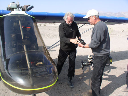 Peter and Les are standing next to a helicopter. Peter is wearing all black and has gray hair. Les is wering a gray sweatshirt, black pants, sunglasses, and a white baseball cap. He is holding a large camera and is handing something black- possibly a small camera-to Peter.