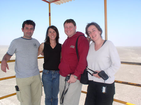 Rich, Tiffiny, James M, and Ruth are standing on a balcony overlooking the Nasca lines. There is a yellow fence along the edge of the balcony. They are facing the camera and smiling. Rich is on the left and is wearing a gray t shirt and khaki pants. He has short brown hair. Tiffiny is wearing a black sleeveless shirt and jeans. She has shoulder length brown hair. James is wearing a red hoodie and khaki pants. He has short brown hair and is holding a small camera. He has a black bag on his shoulder. Ruth us wearing a white long sleeved shrit and black pants. She has shoulder length brown hair. She is holding sunglasses and a camera case. The camera is hanging from her wrist.