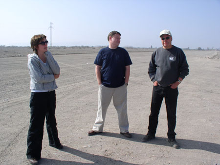 Ruth, James M, and Les are standing on flat rocky ground. Ruth is on the right. She is weraing a gray jacket, blakc pants, and sunglasses. She is looking into the distance and her hand is under her chin. She has chin length brown hair. James is wearing a navy shirt and khaki pants. His hands are in his pockets and he is looking at Les. Les is wering a gray sweatshirt, black pants, sunglasses, and a white baseball cap. He is looking into the camera and his hands are in his pockets.
