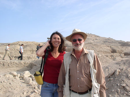Tiffiny and Guiseppe are smiling into the camera. They are on a rocky hill and you can see the peak in the background. There are three people with filiming equipment walking towards the right in the background. Tiffiny is wearing a red tshirt and jeans. She has a yellow bag with a blakc strap on her shoulder. She is holding her shoulder length brown hair behind her ear from the wind. Guiseppe is wearing a brown long sleeved shirt, a white vest, withe pants, sunglasses, and a light brown cowboy-ish hat. He has white facial hair.