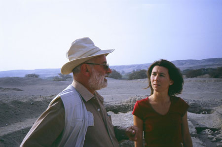 Guisseppe and Tiffiny are talking on uneven rocky ground. There are hills in the distance and the wind is blowing. Guiseppe (on the left) is wearing a brown long sleeved shirt, a white vest, sunglasses, and a light brown cowboy-ish hat. He has white facial hair. Tiffiny is wearing a red t-shirt and her shoulder length brown hair is blowing in the wind.