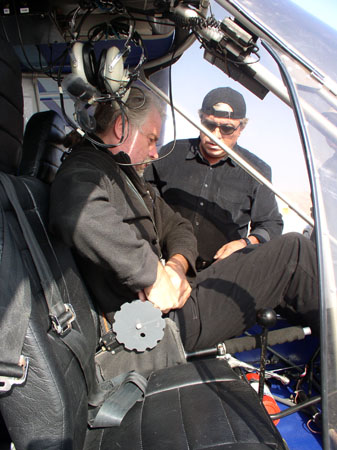 Peter is buckling his seatbelt inside the helicopter. He is wearing all black and has gray hair as well as his beard. There is someone else outside of the helicopter. They are wearing a long sleeved black shirt, sunglasses, and a backwars black baseball cap.