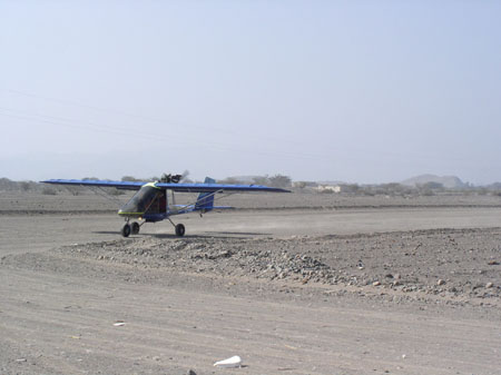 A blue helicopter is sitting on a flat curved path in a rocky landscape. There are small hills in the background.