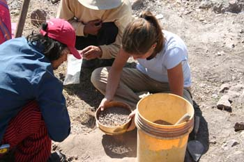 Two people and Luciana on the rocky ground looking into a yellow bowl full of small rocks. There is a large yellow bucket next to them that has a wooden handle coming out of it. The person on the left is wearing a blue long sleeved shirt, red and black striped pants, and a red baseball cap. They have chin length curly black hair. The person in the middle is wearing a yellow sweatshirt, black pants, and a white hat. You can't see their face. Luciana is wearing a white tshirt and khaki pants. Her brown hair is in a ponytail.