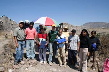 Eleven people standing in a line on a rocky path. There are stone walls in the distance to the right, a multicolored umbrella behind them, a shorter stone wall slightly behind the umbrella, and plants to the right. There is a mountain in the background on the left. The sky is blue. The first person is weraring a gray shirt, jeans, sunglasses, and a white baseball cap. Next, the person is wearing a blue shirt and a white. Next, the person is wearing a red shirt and jeans, and has short black hair. Next, the person is wearing a blue shirt and a red hat. Next, the person is wearing a red and white jacket, jeans, and a gray hat. Next, the person is wearing a green shirt, jeans, and a yellow baseball cap. Next, Luciana is wearing a white shirt, khaki pants, brown hair in a ponytail, and is holding a blue box. The next person is wearing a yellow shirt and khaki hat. The next person is wearing a gray shirt, jeans, and a black baseball cap. The next person is wearing a black long sleeved shirt and khaki pants. They have shoulder length black hair. The next person is wearing a black shirt and khaki pants. They have black hair held back.