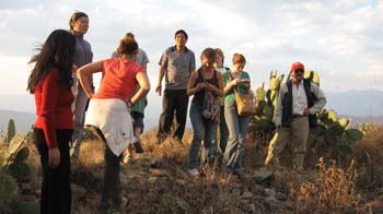 A candid photo of nine people standing on a small rocky hill. There is brown shrubs and cacti around them. The person on the left is wearing a red shirt and black pants. They have black hair past their shoulders. The next person is wearing a gray jacket and has black hair pulled back. The next person is wearing a red t shirt, a white jacket around their waist, and black pants. Their brown hair is in a bun. There is a person eclipsed by the person just described. The next person is wearing a white and black shirt as well as black pants. They have short black hair. The next person is wearing a black tank top as well as jeans, and they have a multicolored bag across their shoulder. They have brown hair pulled back. You can't see the next persons face, but they have brown hair. The next person is wearing a green shirt as well as jeans, and the have a brown bag over their shoulder. They have brown hair in a bun. The person on the far right is wearing a white shirt, black vest, khaki pants, and a red baseball cap.
