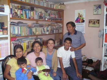Tiffiny with four adults and two children on her left. They are sitting in black chairs in front of a bookshelf. There's two adult on her right. The children are sitting in the adults' laps. The one of the right is wearing a blue shirt and is holding something red. The other kid is wearing a green shirt and a white jacket. They are holding something brown. They both have short black hair and neither of them are looking into the camera. The adult on the far left is wearing a yellow shirt and has brown hair in a ponytail. The next person is wearing a pink shirt and shoulder length black hair. Tiffany is next wearing a blue shirt, brown jacket, and jeans. Her hair is in a ponytail. Next, is a person in a white shirt and jeans. At the far right there's a person in a shirt striped with two different blues and is also wearing jeans.