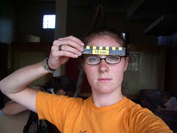 "Cat is looking into the camera and holding up a yellow and black ruler to her forehead. It reads ""15 centimeters."" She is wearing an orange tshirt, black glasses, a gray bracelet, and a brown ring. She has black hair pulled back."